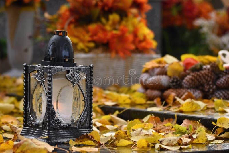 Bello concetto di autunno al cimitero ed al Halloween Candela in una lanterna sulla tomba fondo per Halloween fotografia stock libera da diritti