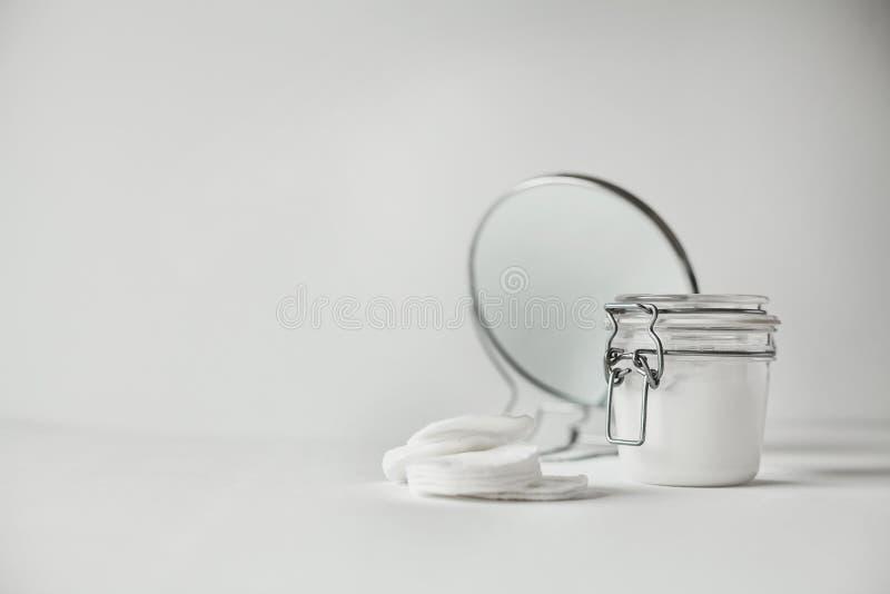 Bello concettuale minimalista tutta la composizione bianca - cuscinetti di cotone, barattolo trasparente e specchio rotondo fotografia stock libera da diritti