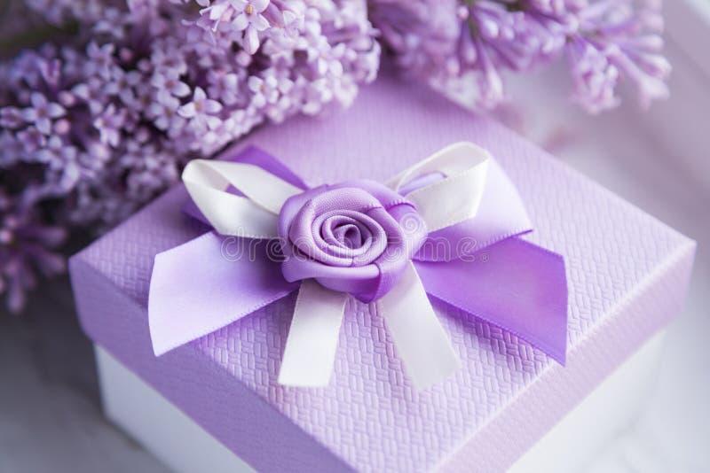 Bello contenitore di regalo con un arco e un lillà di fioritura fotografia stock libera da diritti