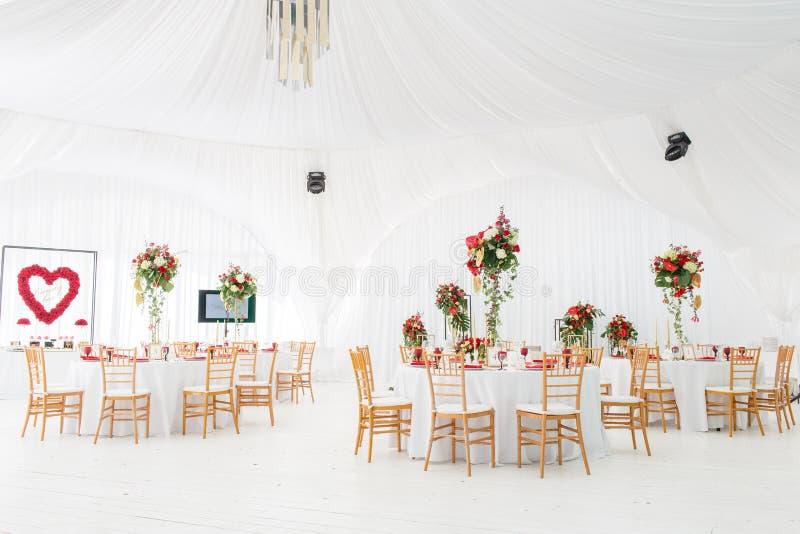 Bello corridoio di banchetto sotto una tenda per un ricevimento nuziale Interno di una decorazione della tenda di nozze pronta pe fotografie stock