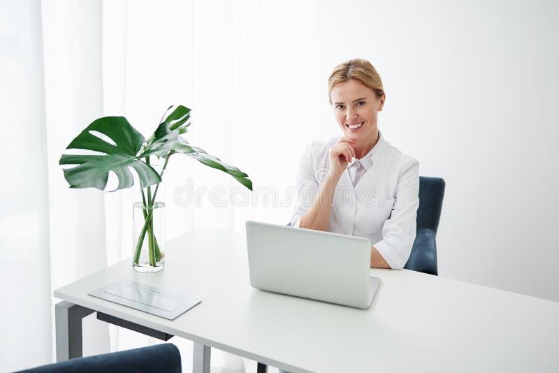 Bello cosmetologo che si siede alla tavola con il computer portatile immagini stock libere da diritti