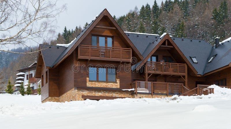 Bello cottage di legno coperto in neve, stazione sciistica Donovaly fotografia stock libera da diritti