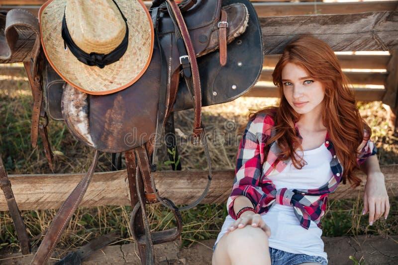 Bello cowgirl della giovane donna della testarossa che si siede all'aperto fotografia stock