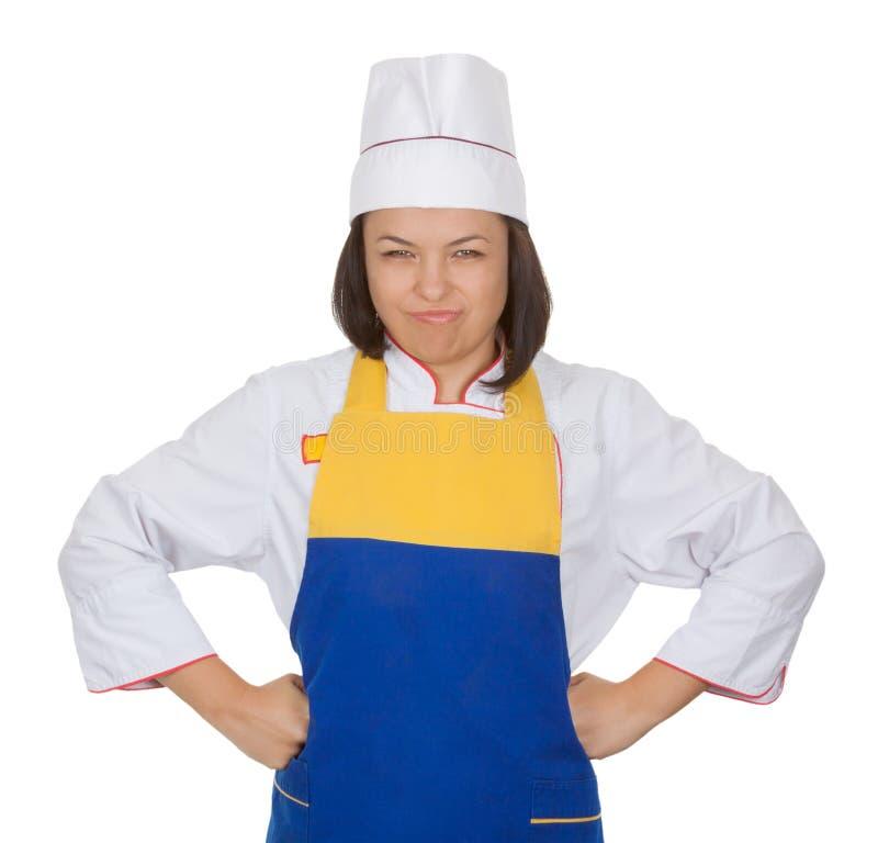 Bello cuoco unico arrabbiato della giovane donna nella cottura dell'uniforme immagine stock
