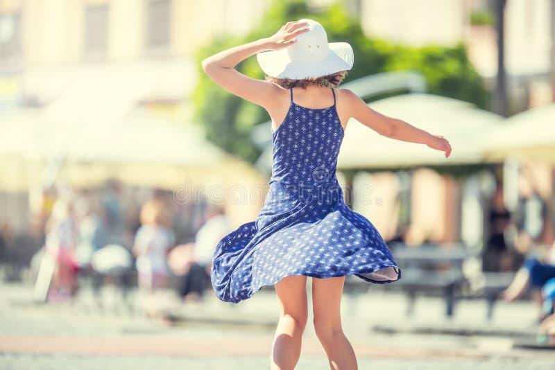 Bello dancing sveglio della ragazza sulla via da felicità La ragazza felice sveglia di estate copre ballare al sole fotografia stock