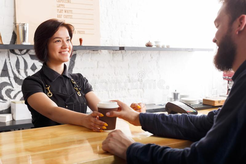 Bello dare sorridente di barista porta via il caffè all'abitudine maschio fotografia stock libera da diritti