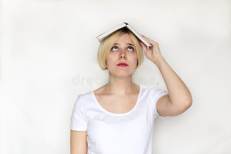 Bello del libro della tenuta della giovane donna del ritratto, della ragazza stanca e del libro di lettura annoiato che studia pe immagine stock libera da diritti