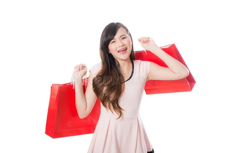 Bello della giovane donna del ritratto che sorride giudicando sacco di carta isolato su fondo bianco fotografia stock