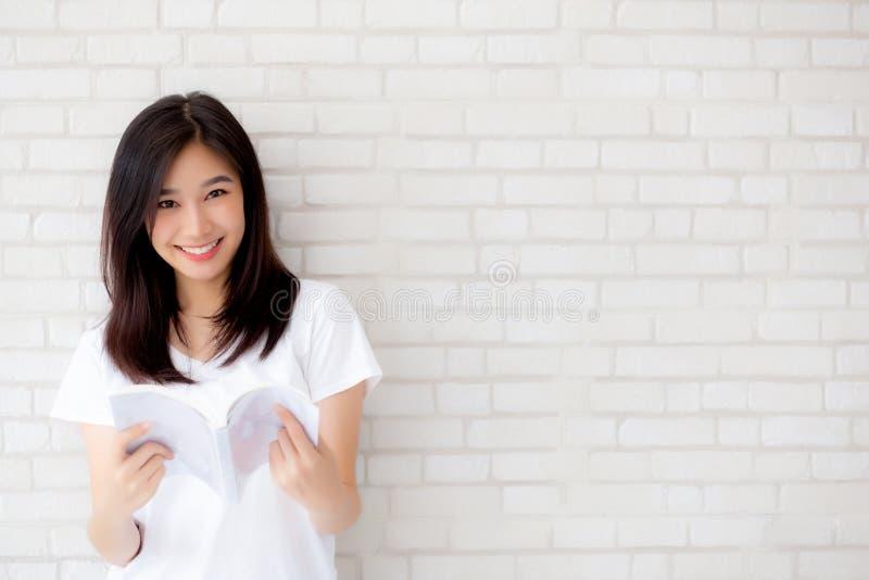 Bello di giovane felicità asiatica della donna del ritratto rilassi il libro di lettura diritto sul fondo concreto di bianco del  fotografia stock