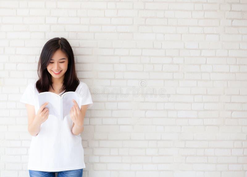 Bello di giovane felicit? asiatica della donna del ritratto rilassarsi il libro di lettura stante sul fondo bianco del cemento co fotografia stock libera da diritti