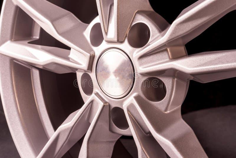 Bello disco fuso d'argento per un'automobile su un fondo nero Fine in su immagine stock