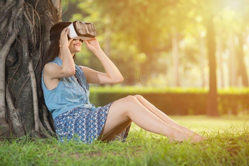 Bello dispositivo asiatico di vetro della cuffia avricolare di esperienza VR della donna immagine stock libera da diritti