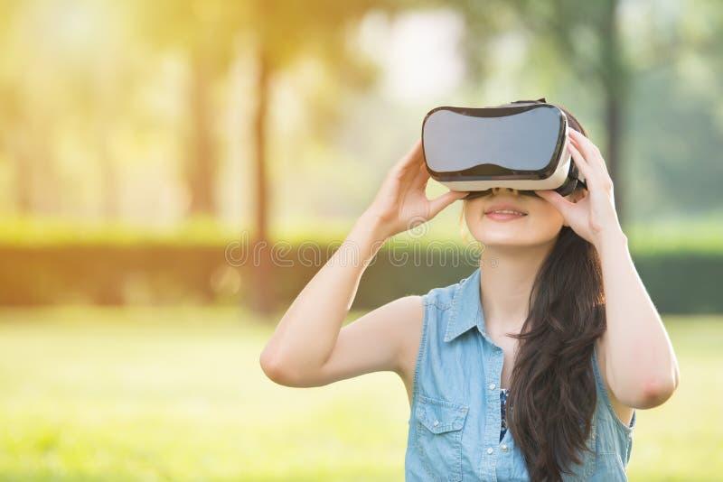 Bello dispositivo asiatico di vetro della cuffia avricolare di esperienza VR della donna immagini stock