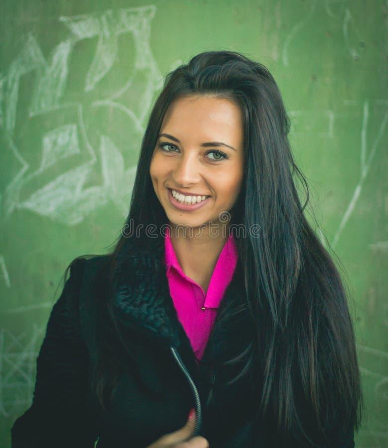 Bello e donna nel peignoir nero con capelli lunghi in una parete verde dei fiori e delle foglie fotografia stock