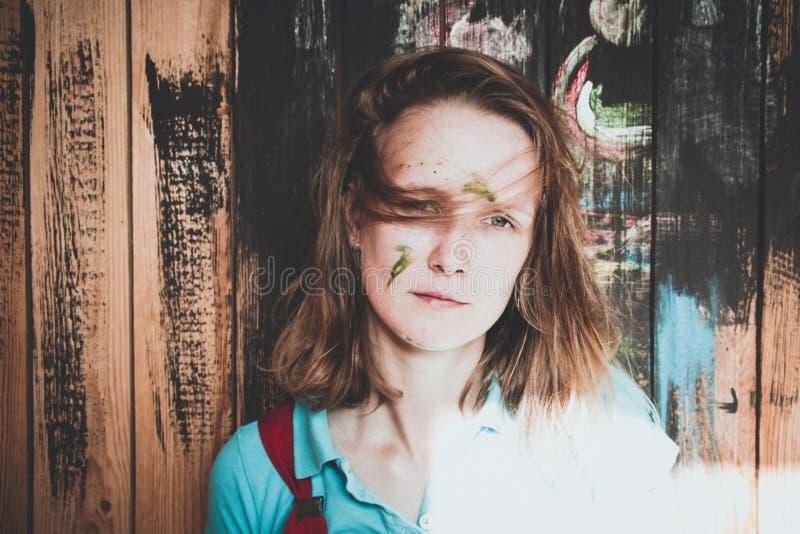Bello e una ragazza con una pettinatura brutta sulla sua testa, supporti sui precedenti di una parete di legno che è dipinta in v immagini stock libere da diritti