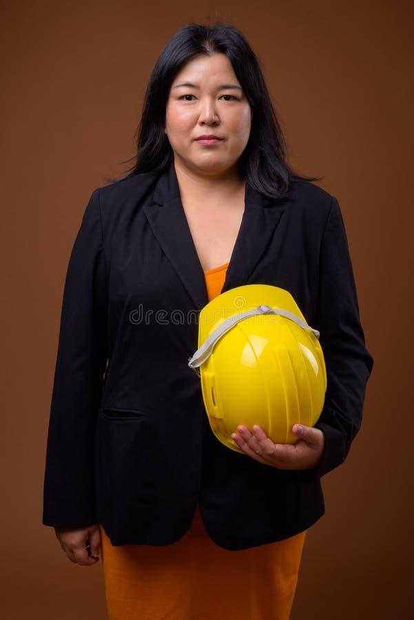 Bello elmetto protettivo asiatico di peso eccessivo della tenuta della donna di affari contro fotografia stock