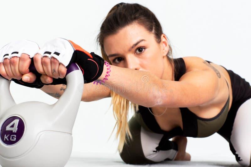 Bello ente di una ragazza di sport che fa allenamento intenso del centro con kettlebell immagine immagini stock