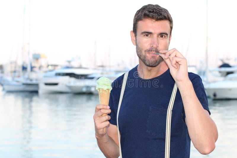 Bello felice maschio mangiando un gelato con un cucchiaio fotografie stock