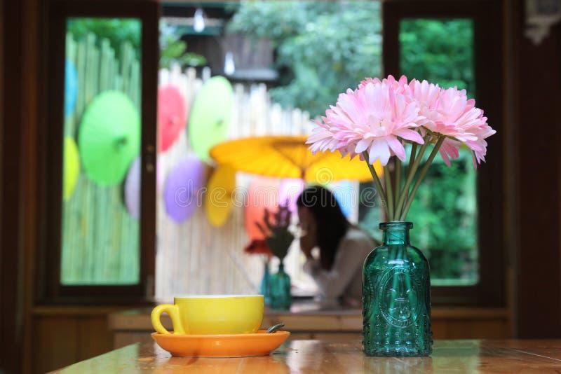 Bello fiore in tazza di caffè e del barattolo sulla tavola di legno con il colo fotografia stock libera da diritti
