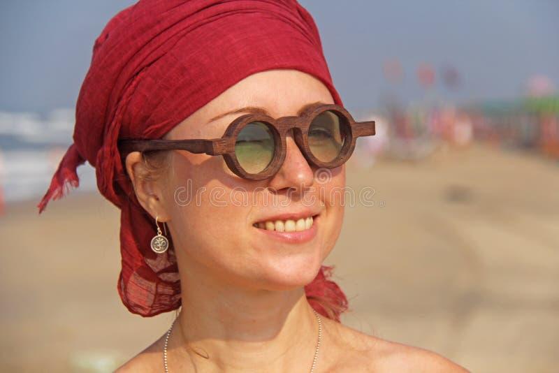 Bello freak della ragazza con un bracciale rosso sulla sua testa, sui precedenti del mare Ragazza di estate in vetri di legno rot immagine stock
