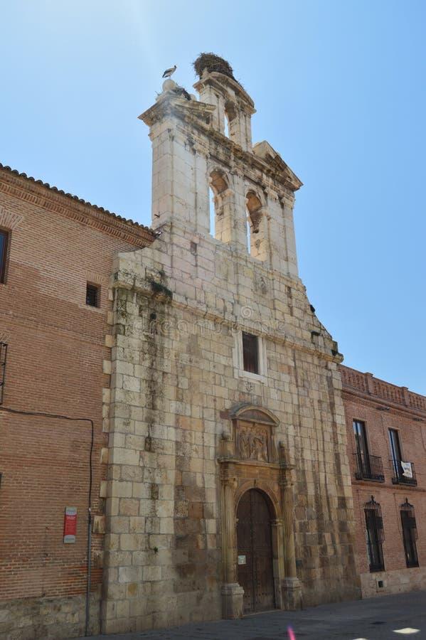Bello Front Facade Of The Church di Alcala De Henares University con un nido delle cicogne nel suo vecchio campanile Architettura immagine stock