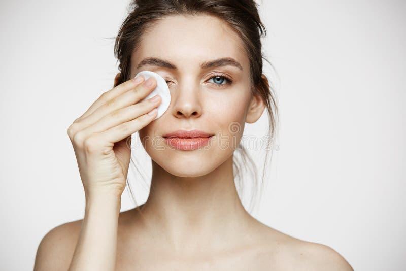 Bello fronte castana naturale sveglio di pulizia della ragazza con la spugna del cotone che sorride esaminando macchina fotografi fotografia stock