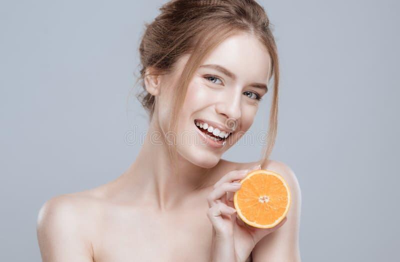 Bello fronte della donna con l'arancia succosa su fondo grigio Bellezza naturale e stazione termale fotografia stock