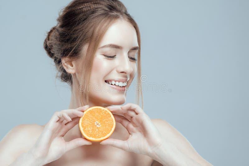 Bello fronte della donna con l'arancia succosa su fondo grigio Bellezza naturale e stazione termale immagini stock libere da diritti