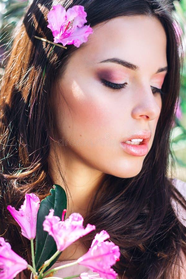 Bello fronte della giovane donna con trucco sopra i fiori rosa Ritratto della ragazza abbastanza in buona salute della pelle este fotografia stock libera da diritti
