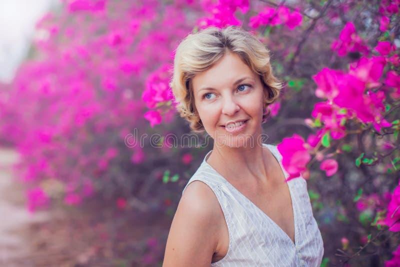 Bello fronte della giovane donna sopra i fiori rosa immagine stock