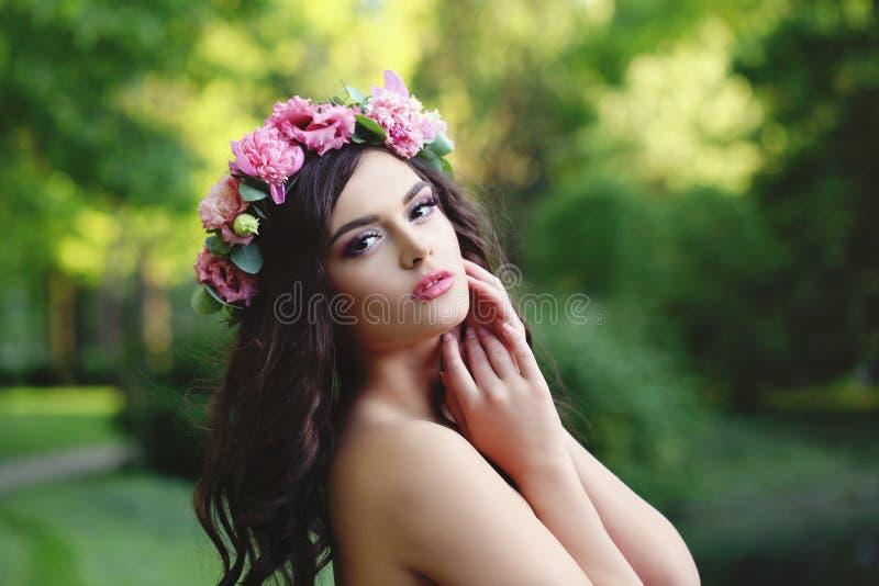 Bello fronte La donna della primavera con capelli lunghi che indossano i fiori rosa incorona immagini stock libere da diritti