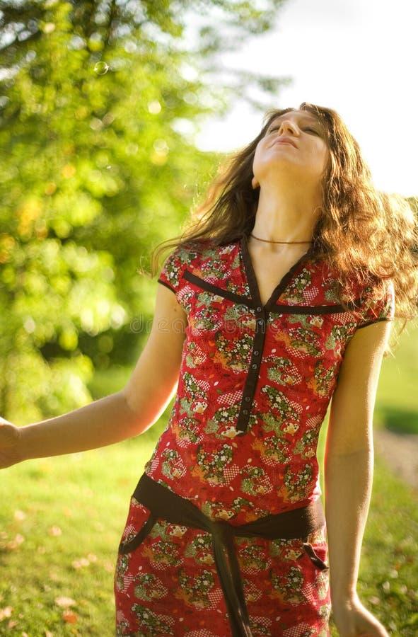bello giorno che gode dei giovani pieni di sole della donna fotografia stock