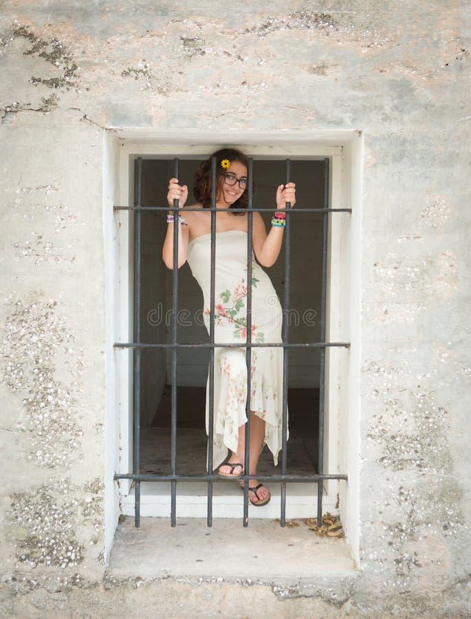 Bello giovane adolescente nella vecchia finestra di pietra della prigione immagine stock libera da diritti