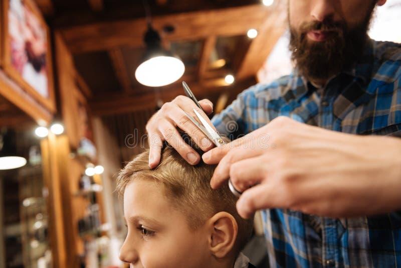 Bello giovane barbiere che usando le forbici fotografia stock
