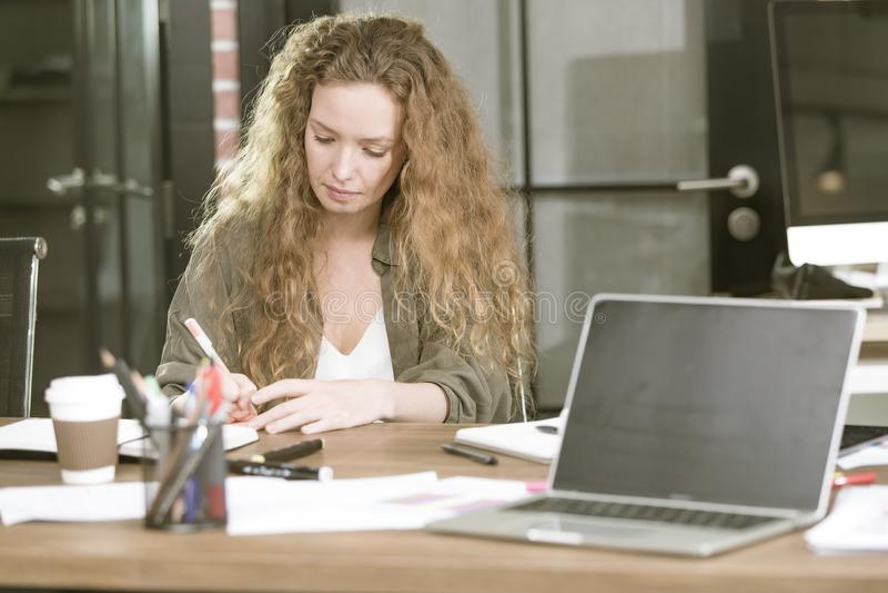Bello giovane businesswomanWorking al suo scrittorio con caffè MU immagini stock libere da diritti
