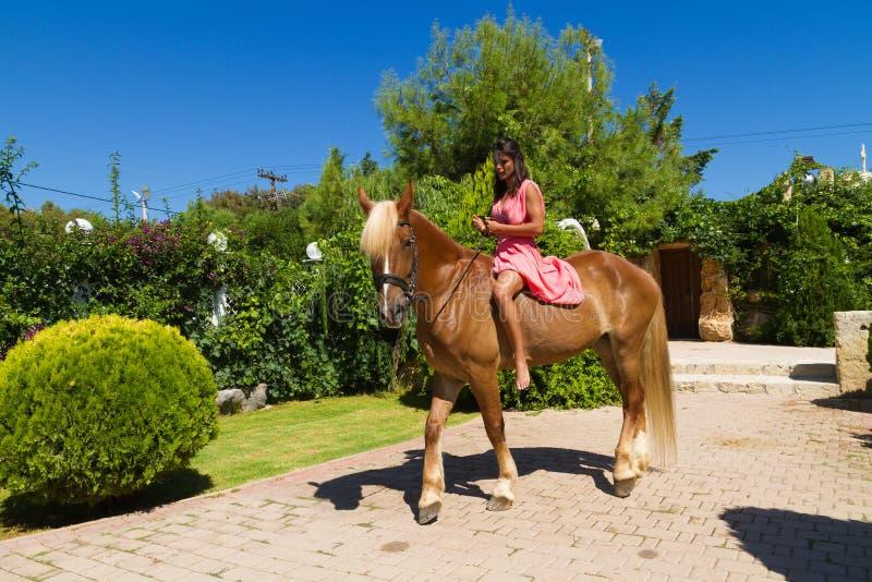 Bello giovane castana con il vestito rosso ed i suoi hors Brown-biondi fotografia stock