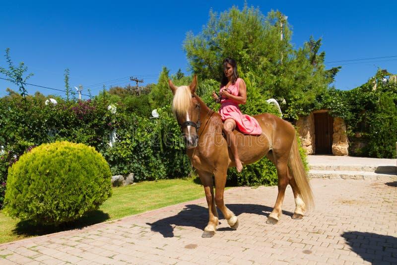 Bello giovane castana con il vestito rosso ed i suoi hors Brown-biondi fotografia stock libera da diritti