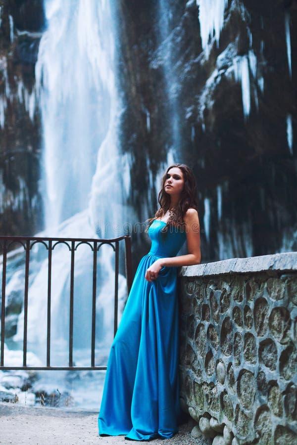 Bello giovane castana in un vestito blu su un fondo di un ghiacciaio e di un massiccio della montagna fotografia stock