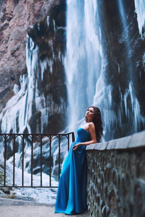Bello giovane castana in un vestito blu su un fondo di un massiccio della montagna e di un ghiacciaio immagine stock libera da diritti