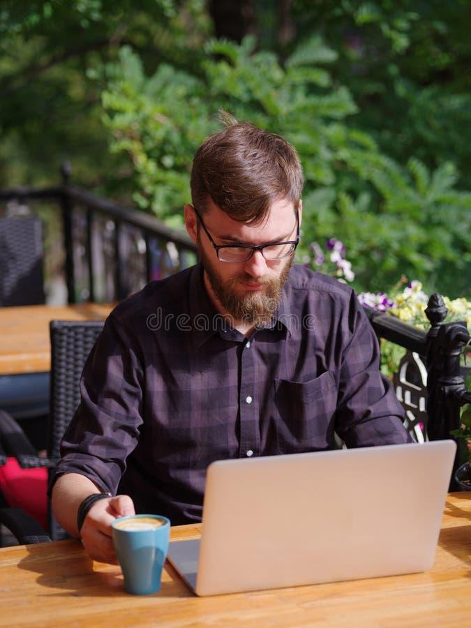 Bello giovane che lavora al computer portatile mentre sedendosi all'aperto Concetto di affari immagine stock libera da diritti