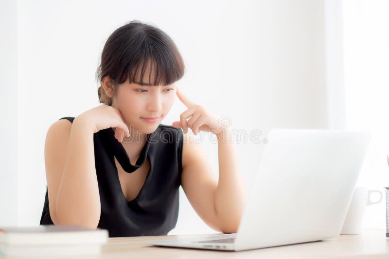 Bello giovane computer portatile funzionante asiatico indipendente di pensiero e di idea della donna all'ufficio fotografie stock