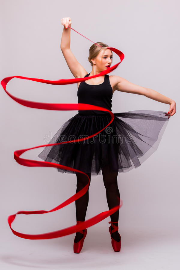 Bello giovane esercizio biondo di calilisthenics di addestramento della ginnasta di balletto della donna con il nastro rosso con  immagine stock