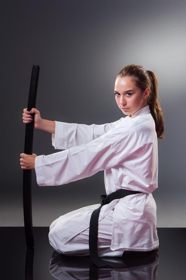 Bello giovane giocatore femminile di karat? che posa con la spada sui precedenti grigi fotografia stock