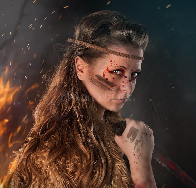 Bello giovane guerriero femminile di Amazon che posa in una posizione combattente con un pugnale fotografia stock libera da diritti