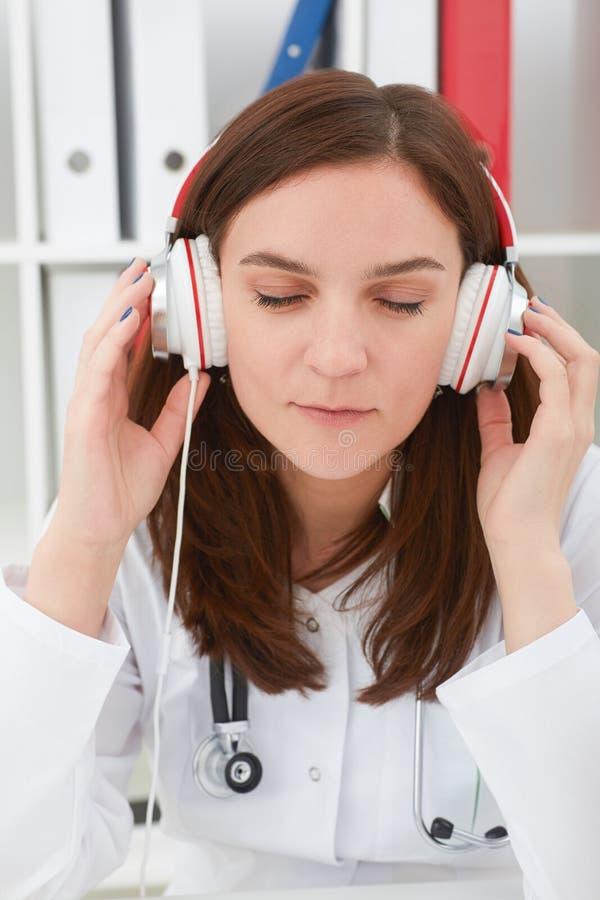 Bello giovane medico femminile della medicina che gode della musica nel suo luogo di lavoro con gli occhi chiusi Medico rilassi i fotografia stock