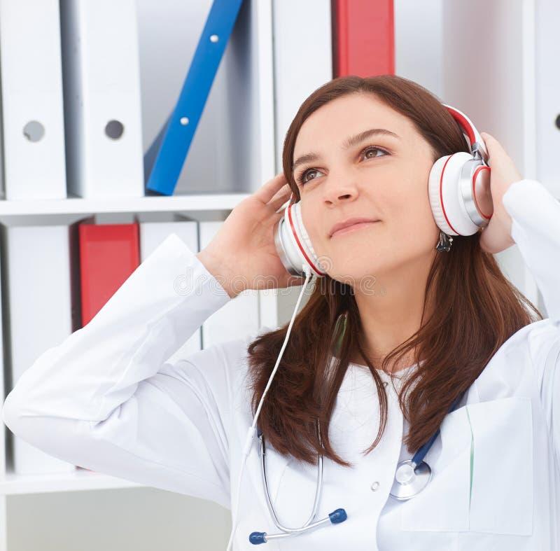 Bello giovane medico femminile della medicina che gode della musica nel suo luogo di lavoro Medico rilassi il concetto fotografie stock