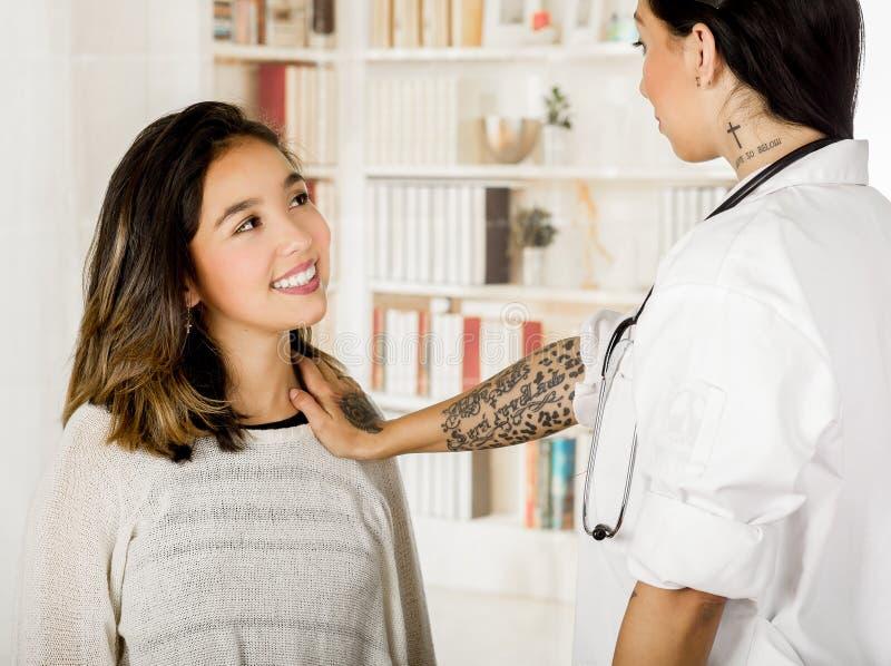 Bello giovane medico tatuato che utilizza la sua mano che controlla il petto del paziente, nel fondo dell'ufficio fotografie stock
