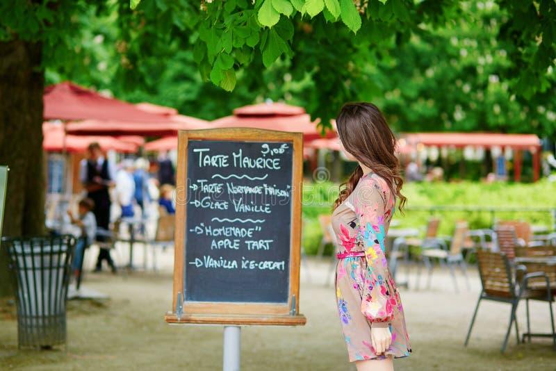 Bello giovane menu parigino della lettura della donna fotografia stock