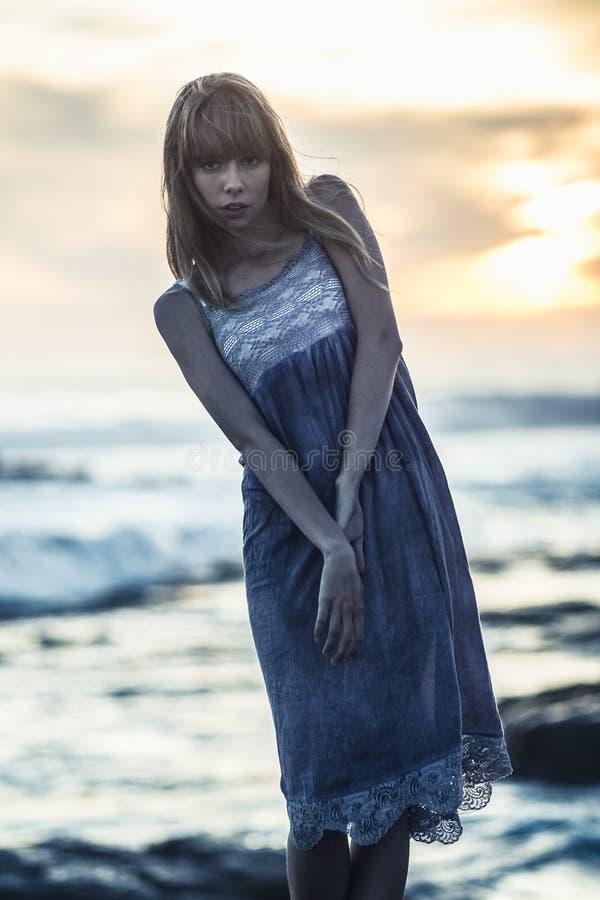 Bello giovane modello che sta sulle rocce dal mare immagini stock libere da diritti