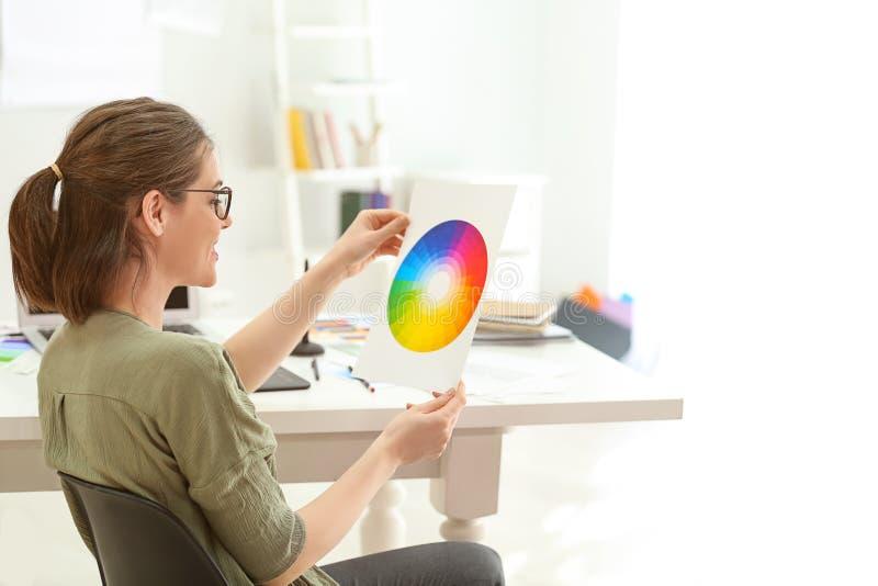 Bello giovane progettista che lavora con la tavolozza di colore in ufficio fotografia stock